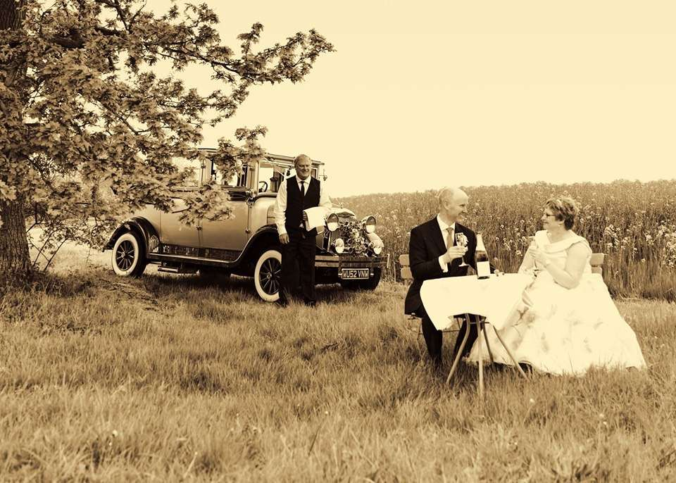 Bride & Groom sat at a table in a field enjoying a glass of bubbly with their wedding car in the background