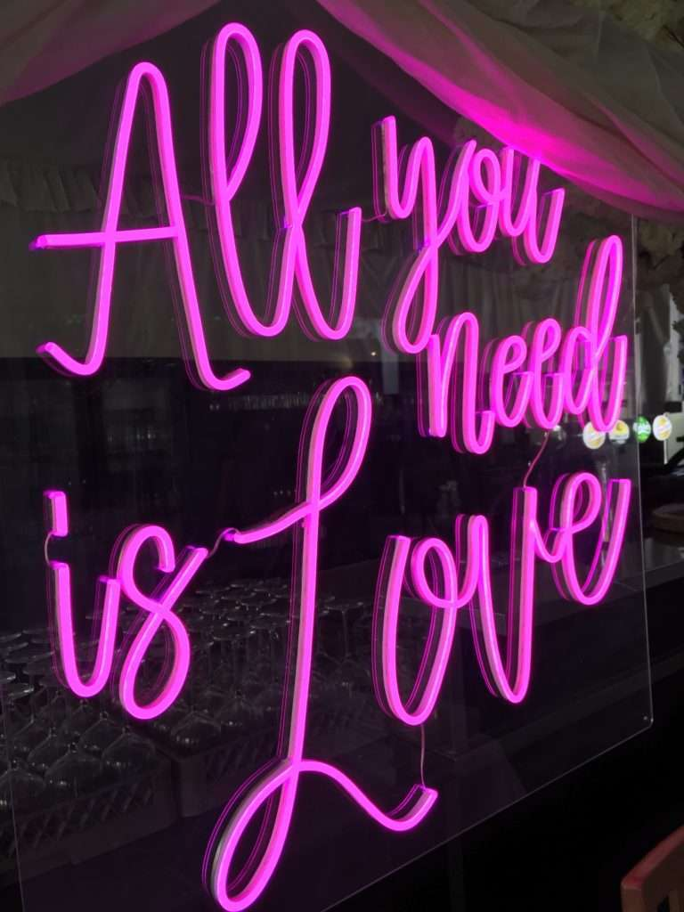 Pink neon writing sign saying all you need is love