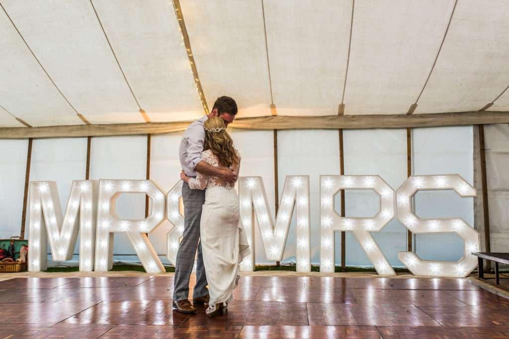 Bride & Groom dancing in front of Mr & Mrs light up letter