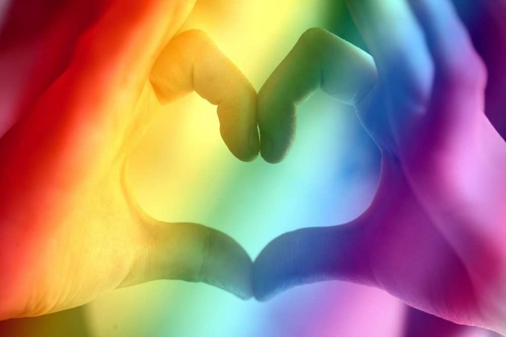 Two hands put together to make a heart with a rainbow filter. The symbol of COVID.